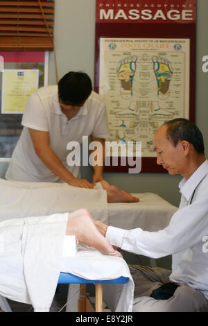 GOLD COAST - SEP 30 2014:Asian therapists gives foot massage.Archaeological evidence of massage has been found in - Stock Photo