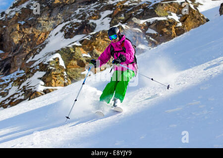 Skier at the turn on mountain steep slope off piste in soft snow on a sunny day on a background of rocks - Stock Photo
