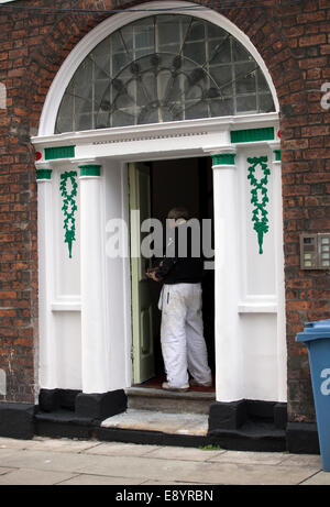 Female painter decorator painting window frame of a garden office stock photo 73336318 alamy for Exterior house painting liverpool