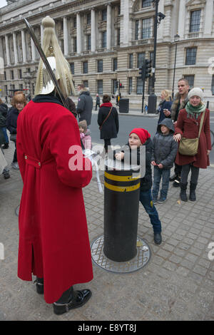 Child pulling faces at a member of the Household Cavalry, Life Guards Regiment, standing guard outside of Horse - Stock Photo