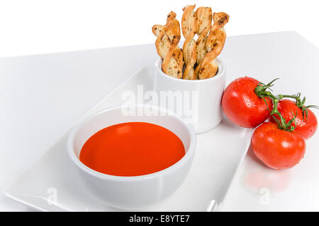 Stock Image - Tomato soup with fresh tomatoes and bread sticks. - Stock Photo