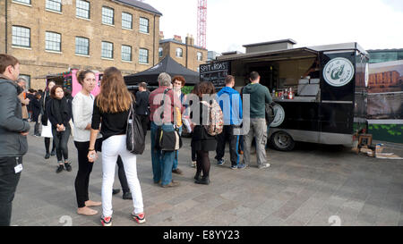 London UK. 16th October 2014. On a warm autumn afternoon people queue to buy lunch from KERB street food vans on - Stock Photo