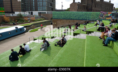 London UK. 16th October 2014. On a warm autumn afternoon people eat lunch from street food vans on the astroturf - Stock Photo