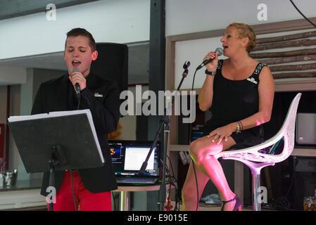 Portugal Algarve Albufeira Da Balaia Club Med Méditerranée GO GO's boy girl man sing singing duet serenade in bar - Stock Photo