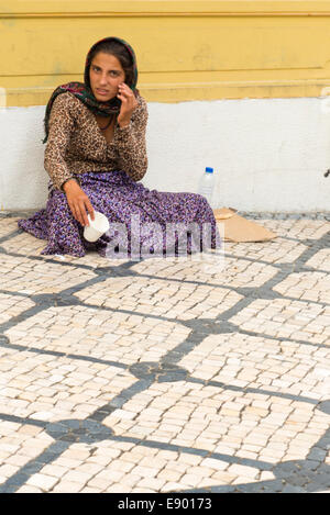 Portugal Lisbon Bairro Alto young female woman girl lady beggar sitting pavement in main pedestrian shopping street - Stock Photo
