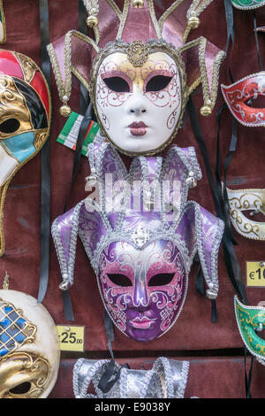 beautiful striking colorful Venetian carnival masks for sale in outdoor tourist market in Piazza di San Firenze - Stock Photo