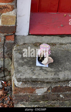A jar of home-made strawberry jam for sale on an honesty box basis at a doorstep in Beaulieu, Hampshire, 2014. - Stock Photo