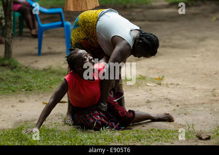 A women calls out in anguish as a relative is removed by healthcare volunteers after being infected by the Ebola - Stock Photo