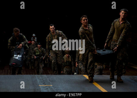 U.S. Marines assigned to the 31st Marine Expeditionary Unit load fuel for combat rubber raiding craft in the well - Stock Photo