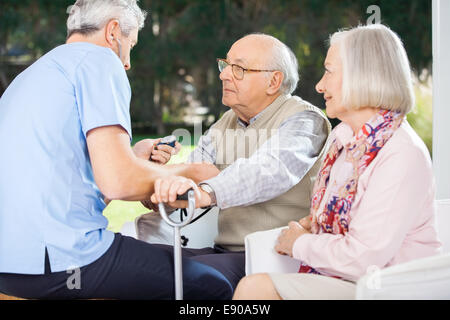 Male Doctor Measuring Blood Pressure Of Senior Man - Stock Photo