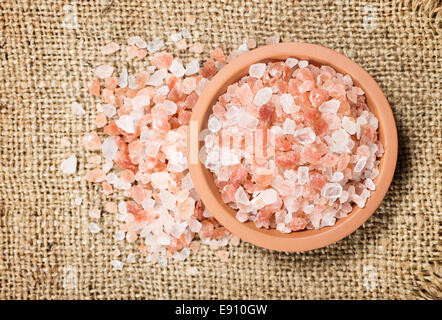 Heap of Himalayan pink salt on jute background - Stock Photo