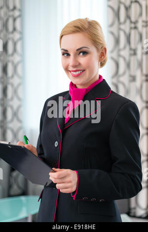 Housekeeping manager or assistant controlling hotel suit or suit with checklist on tidiness - Stock Photo