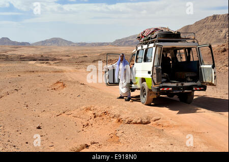 Bedouin Arab man with 4 wheel drive car on off road track in south Sinai desert, Egypt - Stock Photo