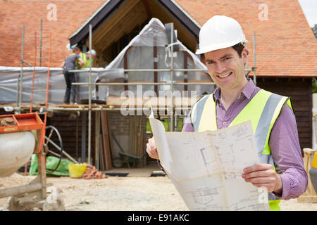 Architect On Building Site Looking At House Plans - Stock Photo