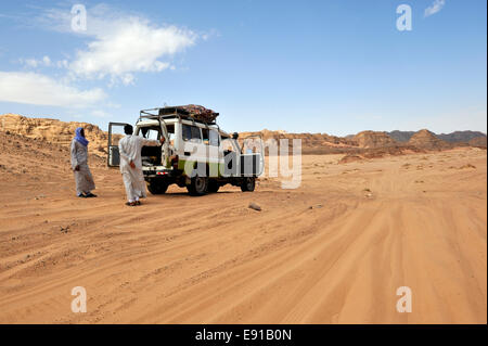 Twp Bedouin Arab men with 4 wheel drive car on off road track in south Sinai desert with doors open for cooling, - Stock Photo