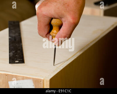 Woodwork tools working on piece of plywood - Stock Photo