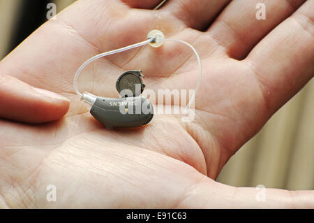 Modern small hearing aid in the palm of a woman - Stock Photo