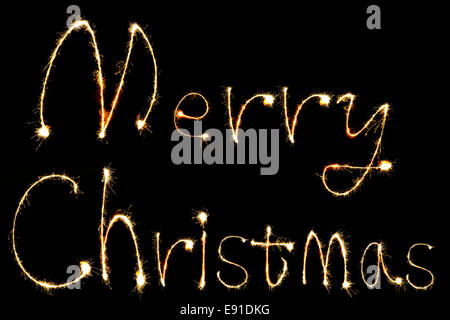 burning sparkler stick and writing Merry Chistmas sparkling words on black background