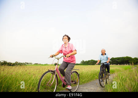 Happy Asian elderly seniors couple biking in the park - Stock Photo