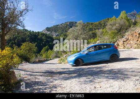 Alaró, Mallorca, Balearic Islands, Spain. Blue car taking bend on descent of narrow country road. - Stock Photo