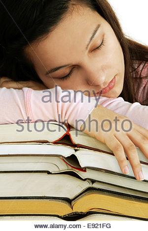 Tired girl sleeping on books stack - Stock Photo