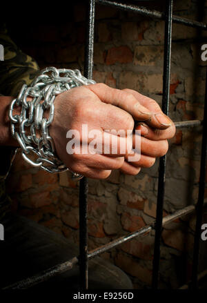 Man with hands tied up with chains - Stock Photo