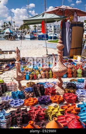 Souvenir Tunisian ceramics displayed on the ground in Port el Kantoui in Tunisia. - Stock Photo