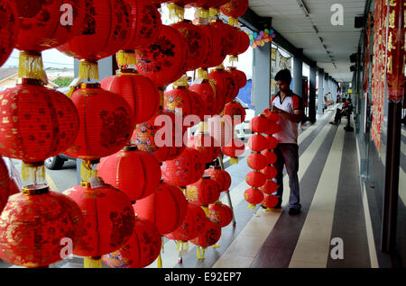 Worker hanging up Chinese new year red lanterns in shop front - Stock Photo