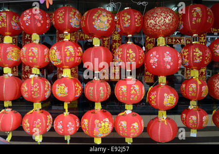 Rows of Chinese New Year red lanterns hanging in shop front - Stock Photo