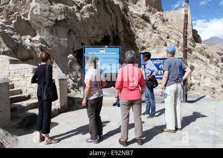 Tourists at the visitor information sign at historic Shey Palace near Leh in Ladakh - Stock Photo