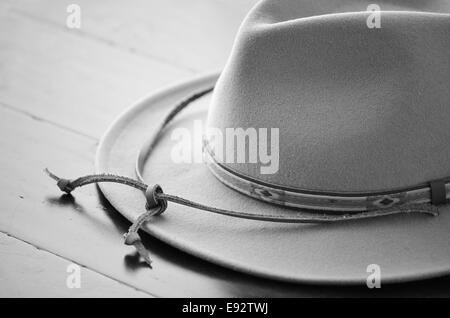 Cowboy hat in black and white on wooden background in horizontal format with selective focus - Stock Photo