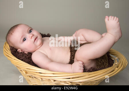 9 month old baby boy laying on his back in a basket - Stock Photo