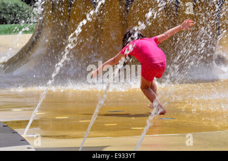 Child (girl age 04) play with water fountain. concept photo hot weather and heatwave. copyspace - Stock Photo