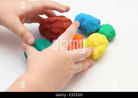 Children's hands playing with play clay. - Stock Photo