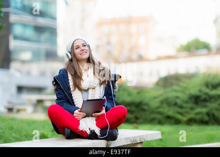 Portrait of teenage girl listening music - Stock Photo
