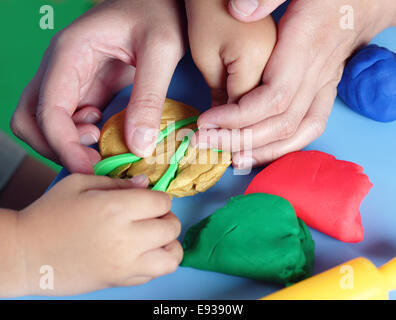 Children's and mother's hands playing with play clay. - Stock Photo