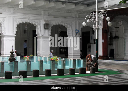 A man washes before praying at the Jummah Masjid (mosque) in Port Louis, Mauritius - Stock Photo
