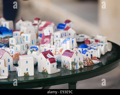 Browsing or buying souvenirs is a part of vacation in the Greek islands, white miniature houses displayed in the - Stock Photo