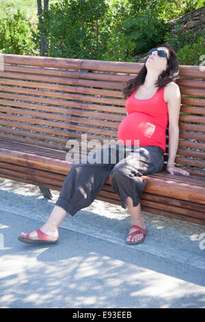 pregnant woman tired sitting on a bench resting - Stock Photo
