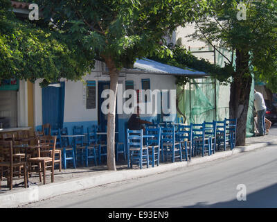 Typical Greek pavement café, colourful blue wooden tables and chairs, Pythagoreion village in the island of Samos - Stock Photo