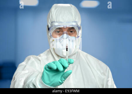 Scientist in protective gear holding syringe with blood droplet on needle - Stock Photo