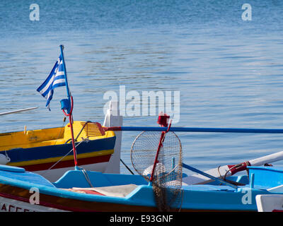 Fishing boat in the harbour of Pythagorion in Samos island Greece. Blue colours of sea, Greek flag and boat, holiday - Stock Photo