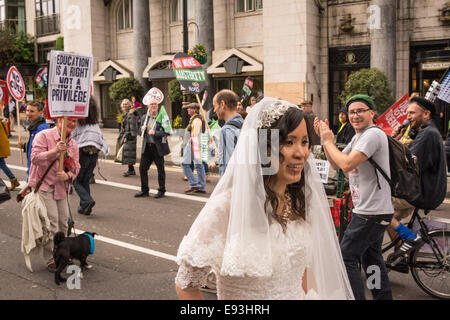 London, UK, 18th October 2014. A new bride gets caught up among crowds during the 'Britain needs a pay rise' march - Stock Photo