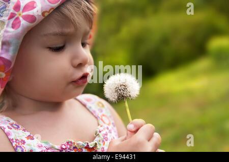 Little Cute Girl Blowing On A Dandelion In The Field - Stock Photo