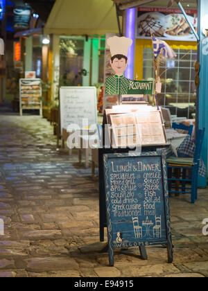 Late evening in the harbour of  Pythagorion on Samos island in Greece, a range of restaurants offering local food - Stock Photo