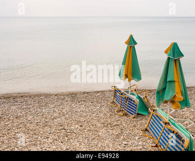 Bleak day on a beach, empty sunbeds, closed parasols, gray skies nobody playing in the water or with the pebbles, - Stock Photo
