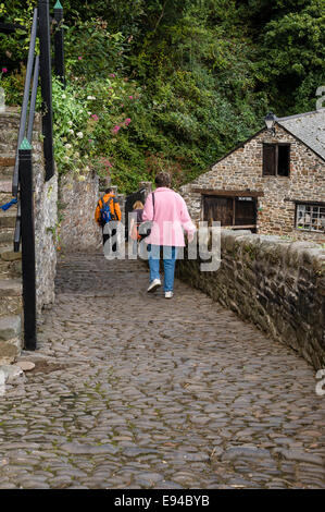 Walking down the steep, cobbled street towards Clovelly harbour. - Stock Photo