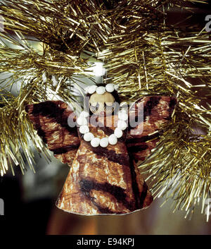 A Hawaiian angel Christmas ornament of tapa cloth with a lei of seashells around her neck hangs in a Christmas tree - Stock Photo