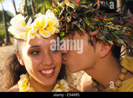 A Hawaiian female hula dancer gets a kiss on the cheek from her fellow entertainer after their performance at a - Stock Photo
