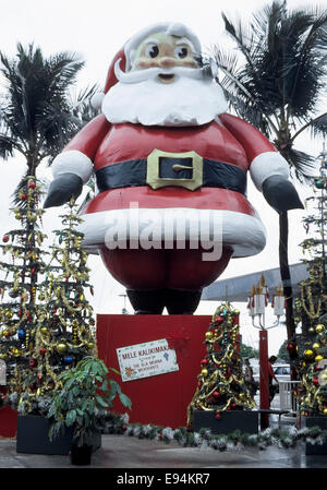 A towering Santa Claus display wishes shoppers a Hawaiian Merry Christmas (Mele Kalikimaka) at the Ala Moana Center - Stock Photo